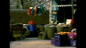 filistin : BETHLEHEM, WEST BANK, ISRAEL- CIRCA 1979: street seller of clothes in the old local market of the town. Historic archival footage of Israel and Palestine in the 1970s. Stok Video