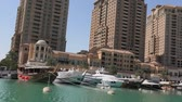 Doha, Qatar - February 18, 2019: Marina corniche promenade with luxury boats and yachts in Porto Arabia at the Pearl-Qatar. Residential towers on background. Persian Gulf, Middle East. Sunny blue sky.