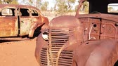rottami : SLOW MOTION: Sunbeams of sunset on rusty wrecks of old cars. Australia, Northern Territory in Red Centre desert. Filmati Stock