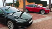 crossover : Menton, France - March 3, 2018: - Luxury Black Tesla Model S And Red Tesla X Model Electric Cars Parked on a Square in Menton on The French Riviera - 4K Video Stock Footage