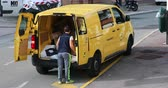 porte aperte : Roquebrune-Cap-Martin, Francia - 14 novembre 2018: The Yellow Post Parcel Van Service Delivery (Citroen Jumpy) e Dipendente in strada. The Post è una società di servizi postali in Francia - Video DCi 4K Filmati Stock