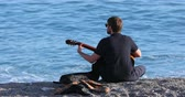 Menton, France - December 4, 2018: Young Man Playing An Acoustic Guitar On The Beach, Mediterranean Sea, French Riviera, Europe - DCi 4K Resolution