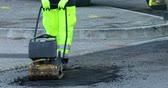 vrak : Roquebrune-Cap-Martin, France - December 5, 2018: Asphalt Worker At Road Repairing Manual Compactor Plate, Closeup View - DCi 4K Video