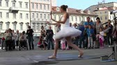 tutu skirt : TRIESTE, ITALY - SEPTEMBER 28: Female ballet dancer wearing a white tutu and pointe shoes dancing in the street on September 28, 2014 Stock Footage