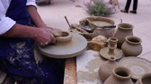 article : Pottery maker uses a kick wheel to hand mold a pot from clay