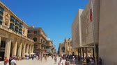máltai : Valletta, Malta pedestrian zone and traditional Maltese buildings of historic city with crowd. Exterior day view of the new Parliament House after City Gate entrance, on a sunny day. Stock mozgókép