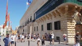 maltês : Valletta, Malta Grandmasters Palace facade in St Georges Square. Day view of the Governors Palace with traditional Maltese architecture and tourists at the square on Republic Street.