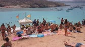 maltês : Comino Island, Malta tourists swimming at the Blue Lagoon. Day view of unidentified crowd sunbathing at the rocky hill of the most famous and crowded beach in Malta with crystal clear waters.
