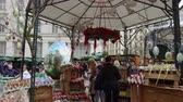 сувениры : Vienna, Austria Easter Market Altwiener Freyung Ostermarkt. Crowd at Wien, Osterreich 2019 street market, where local vendors from Austrian regions sell decorative Easter eggs, food & drinks. Стоковые видеозаписи