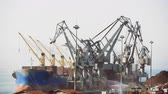поднятый : Large motorized cranes on sea port unloading cargo from ships. Elevated view of ship to shore cranes handling cargo on commercial berthing dock pier of Thessaloniki Port, Greece.