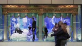 vitrine : Christmas shop window showcase with passing crowd. Decorated Christmas 2019 facade of Attica department store at Tsimiski street in Thessaloniki, Greece. Stockvideo