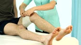 Physiotherapy doctor bandaging patient leg film
