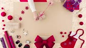 Woman tying a ribbon around Christmas present Stock Footage