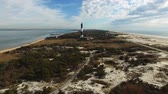 horizont nad vodou : Aerial View of a Lighthouse and Shoreline Close Up on a Sunny Winter Day as Seen by a Drone Dostupné videozáznamy