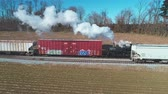 cargo container : Strasburg, Pennsylvania, February 2019 - Aerial View of a Steam Freight and Passenger Combo Train as Seen by a Drone on a Sunny Winter Day