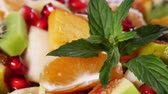 citrus fruit dish : Top view of a fruit salad with mandarin, oranges, kiwi, pomegranate seeds, figs, banana and peaches