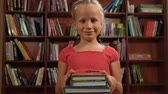 coletas : six year old girl standing with books and smiling Archivo de Video