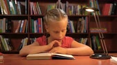 libro : six year old girl reading sitting at the table by the light of a desk lamp