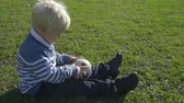 calcetto : three year old boy sitting on the green grass on a sunny day with a soccer ball Filmati Stock
