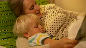 literatuur : mother and baby son reading a book in bed Stockvideo