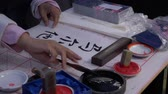 caligrafia : Slow motion, close-up shot of hand using a large ink brush to write traditional Japanese calligraphy