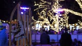 danimarka : Christmas ice skating rink and sled at market square fair in Austria Viena night time with winter decoration and colourful lights Stok Video