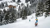 powder snow : Children skiing in Switzerland in Villars-sur-ollon in the Vaud county, zoom in Stock Footage