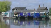 calm : Blue narrow boats in a row at moorings on canal Stock Footage