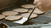 charbroiled : barbecue scene burgers flipped over with a tong spatula turner on the grill over a calm fire flame