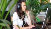 executive : Woman talking on headset in office with client surrounded by plants Stock Footage