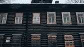 bez domova : Old wooden house with black windows. Nobody inside. Abandoned house in disrepair with boarded-up windows in Pereslavl-Zalessky city, Russia Dostupné videozáznamy
