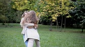 sarılma : two beautiful happy young women meet and hug Stok Video