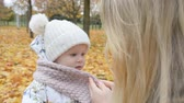 pano : mother care and love concept, mom wraps her little daughters scarf in autumn park hd stock footage