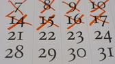 datum : STOP MOTION: Crossing out (red marker) a numbers in a calendar page - Macro hd stock footage, past days