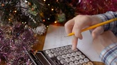 a man hands near a decorated Christmas tree and considers the budget, the cost of New Year or christmas gifts to his family and colleagues at work
