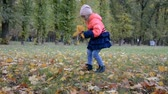 omuz : two little girl five years old play with leaves in the park in the fall Stok Video