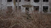 Two soldiers make their way through the bushes against the backdrop of an abandoned two-story building hd stock footage