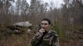 meslek : young soldier talking on the walkie-talkie in the autumn forest, military concept
