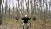 udatnost : The guy is sitting with a barbell in the forest, sports concept