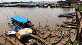 cambojano : A fluvial port in Cambodia with a man and a woman starting to sail on a river MF
