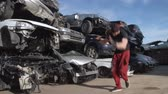 A break dancer is training in a junkyard doing some jump on one hand. FDV