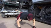A young man is training by jumping push ups at a junkyard. FDV