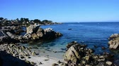 Calm waters in Monterey Bay. Rocks in the foreground and Pacific Grove behind. Camera locked.