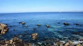 amantes : Calm waters in Monterey Bay as water laps at the rocks on the beach. Camera panning right to left. Stock Footage