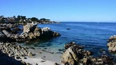 Calm waters in Monterey Bay as water laps at the rocks on the beach. Camera panning left to right. Stock Footage