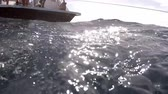 girme : A scuba diver entering the water off of a drive boat with other divers. Stok Video
