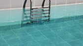 Water splashing in the outdoor swimming pool with metal ladder Стоковые видеозаписи