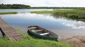 Fishing boat moored on the lake in the morning in summer sunny day. Summers lake scenery