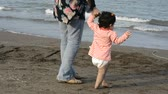 first child : Back view of mother and young child with diaper walking at beach, one years old first experience in toddling, parenting and teaching concept Stock Footage