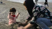 first child : Mother and young child playing with sand at beach, care and watchfulness concept